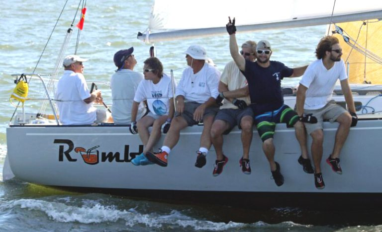 Crew from the boat Rumbles giving the peace sign during Southern Bay Race Week
